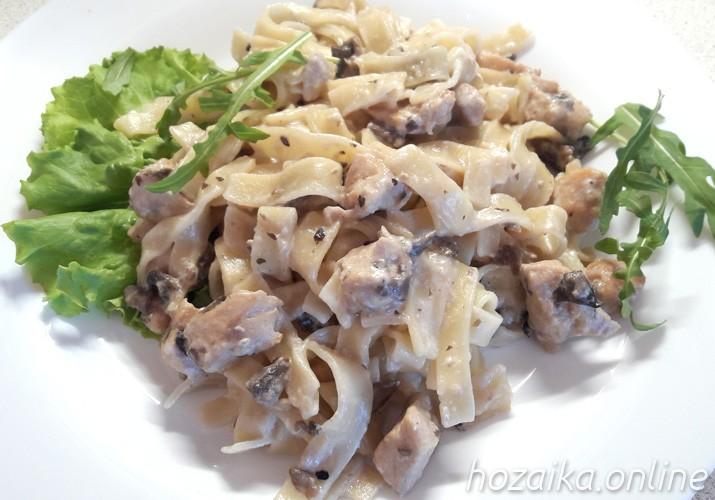 Сливочная паста с курицей и грибами на тарелке