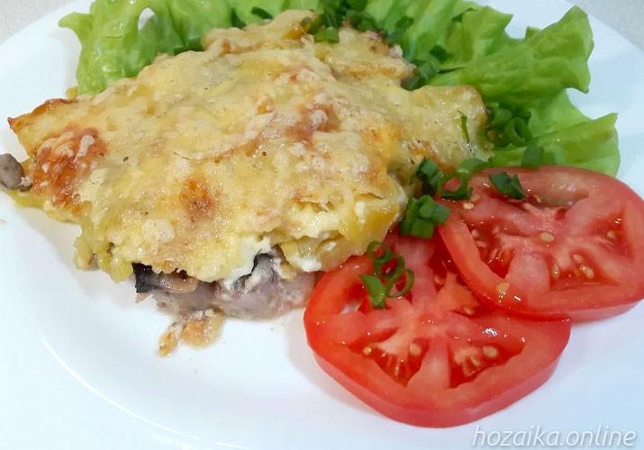 мясо по-французски с грибами и сыром на тарелке