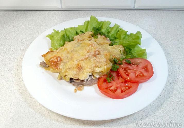 мясо по-французски со свининой и грибами на тарелке