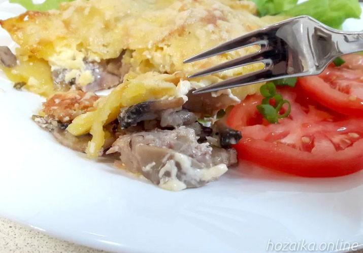 мясо по-французски со свининой и грибами на тарелке в разрезе