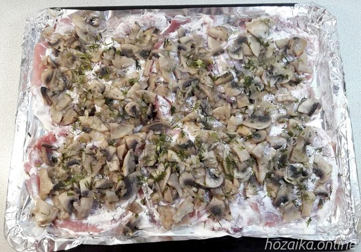 слой грибов на отбивных из свинины